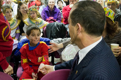 Mayor Nir Barkat shakes the hand of a boy in a race car driver costume in a special Purim reading of the Book of Esther for the deaf and hearing-impaired at Bet Zusman using special amplifiers, visual projection and simultaneous sign language translation. Jerusalem, Israel. 8-Mar-2012.