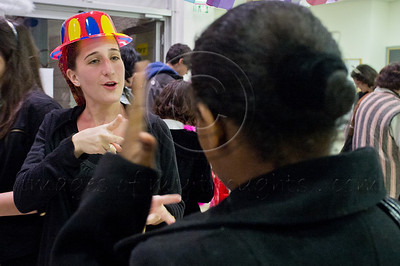 Municipal social worker Merav uses sign language to communicate with patients as Purim celebrators assemble at Bet-Zusman for a special reading of the Book of Esther for the deaf and hearing-impaired. Jerusalem, Israel. 8-Mar-2012.