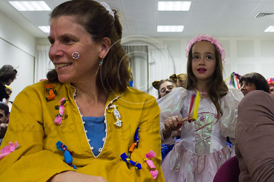 A young girl uses a special Purim noisemaker to drown out the name of Haman at a special Purim reading of the Book of Esther for the deaf and hearing-impaired at Bet Zusman. Jerusalem, Israel. 8-Mar-2012.