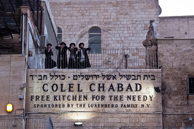 Ultra-Orthodox Jewish men stand on a balcony in the Jewish Quarter and view a welcoming ceremony for thousands of swifts returning from South Africa to nest in the Western Wall as spring and breeding season arrive. Jerusalem, Israel. 12-Mar-2012.