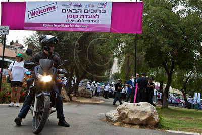 Policemen on motorcycle provide security as women of all ages and races take part in a festive celebration of femininity at Sacher Park prior to the start of Komen's second annual Israel Race for the Cure. Jerusalem, Israel. 3-May-2012.